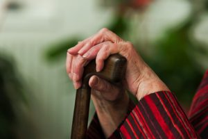 Older persons hands holding onto walking stick close up