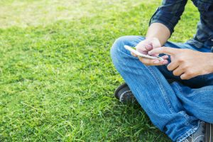 man sitting on grass with mobile phone
