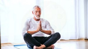elderly man meditating on floor and mat at home
