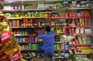 man at grocery store in India looking at products on shelf