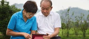 elderly couple outside on tablet computer