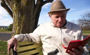 elderly man outside sitting on bench with mobile phone