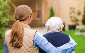 elderly woman supported by carer