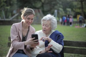 elderly woman with female carer outside looking at phone