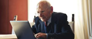 elderly man at table with laptop