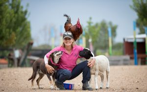 volunteer with a dog, chicken and goat outside in a field