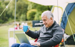 senior man sitting outside a tent with his laptop and a mug in his hand, smiling