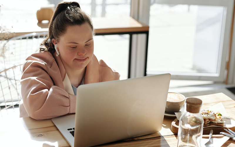 women sitting at desk with a laptop computer and headphones in ears