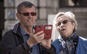 elderly couple looking at mobile phone