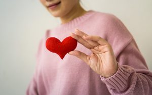 lady in pink sweater holding a red heart