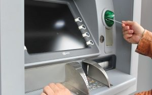 atm with hand using card slot