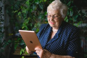 elderly lady sitting and holding tablet, smiling
