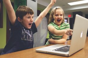 children on computer looking excited