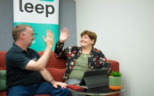 a man and a woman sitting on a couch with a laptop, high five with hands