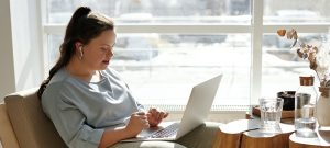 woman sitting on armchair with laptop and airpods
